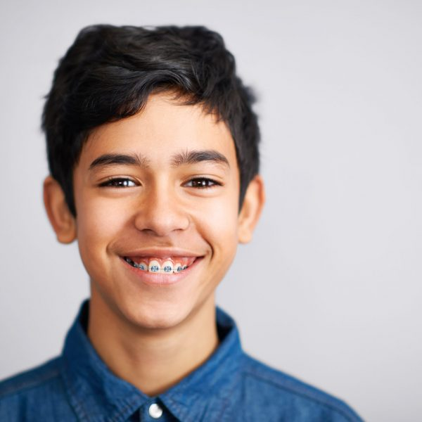 A cute young preteen boy standing and smiling against a grey background